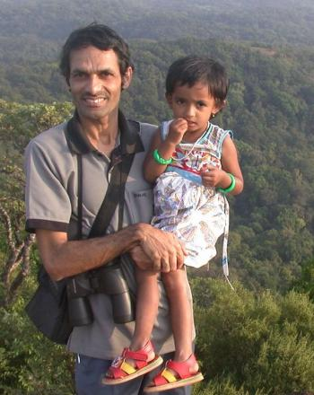Smiling man holds young daughter above lush background.