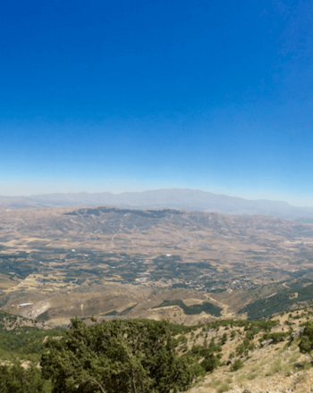 High-up view of the landscape and bright blue sky.