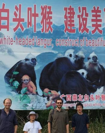 Large sign, four people standing underneath.
