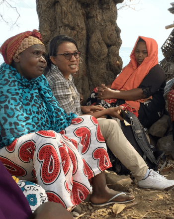 Small group of women, most in bright, patterned clothes, sitting outside, water in background.