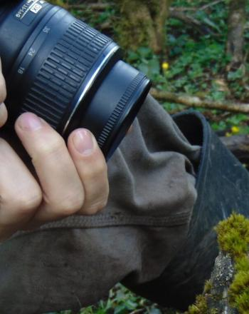 Close-up of photographer photographing very small frog.