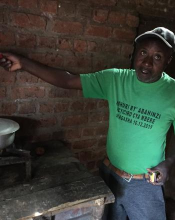 A man shows a biogas-powered stove set up on a table next to him