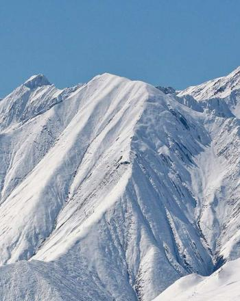 Close-up of snow-covered mountains ridgeline.