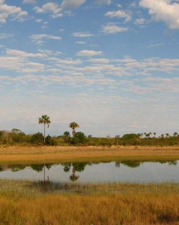 Flat orange landscape, small body of water, vast sky.