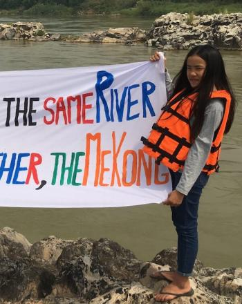 "Two girls standing in front of river holding hand-made sign that says ""Lancang-MEkong is the Same River We Share the Same Mother, the Mekong"""
