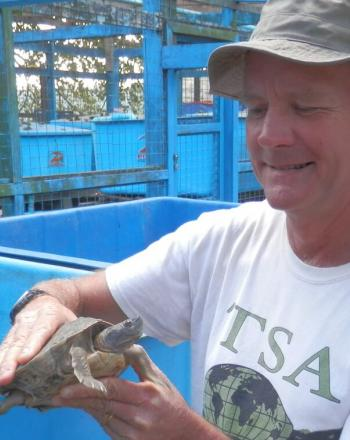 Man with TSA shirt holding small turtle.