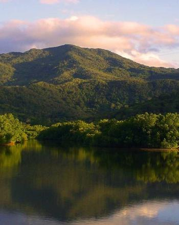 Dark water in the foreground, lush hills in the background.