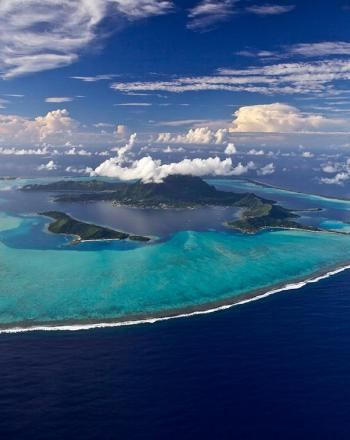 Island surrounded by sand-fringed islets and a turquoise lagoon.