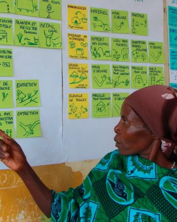 Woman pointing to colorful notes on a wall.