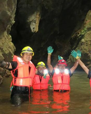 Five people wearing helmets and orange vests in cave, waist-height in water, smiling, waving at camera.