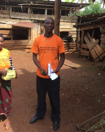 A man and a woman stand in front of a cattle shed