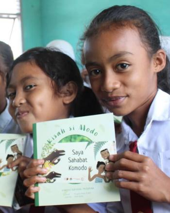 Five girls holding Komodo dragon educational books.