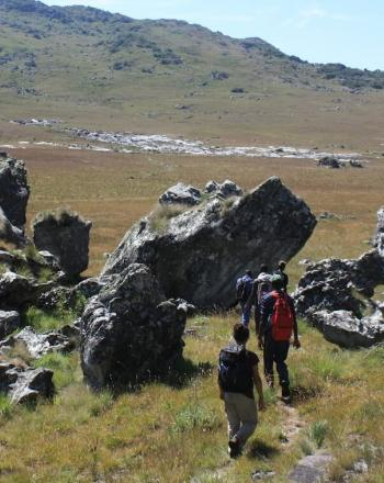 Small group of people hiking amid large, jagged ricks and, in the background, hills.