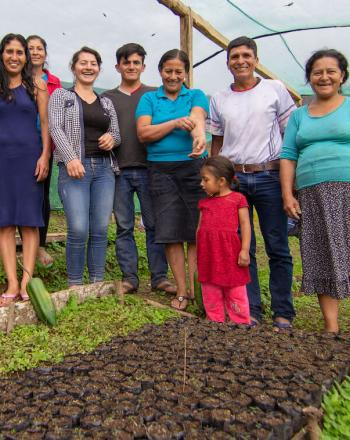 Eight people, including one small child, standing and smiling at camera within a tree nursery.