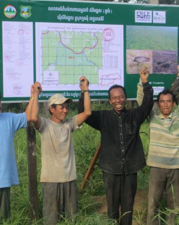 Group of 5 men standing outside, holding hands in the air and smiling in front of signboard with map.