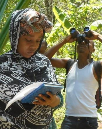 Woman looks at notebook while holding device up while man behind her looks through binoculars.