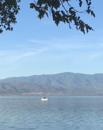 Lake vista, one boat in distance and mountains in background