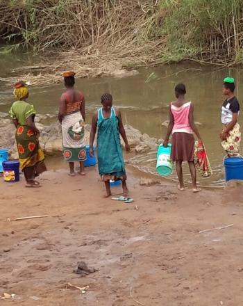 Six women washing laundry along the riverside.