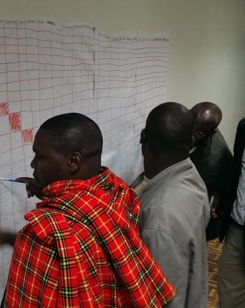 Four men looking at hand-written chart on wall.