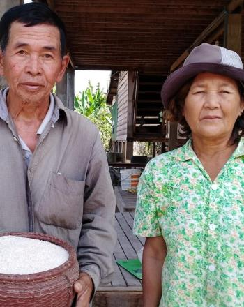 Man holding rice stands next to woman. They both are facing the camera.