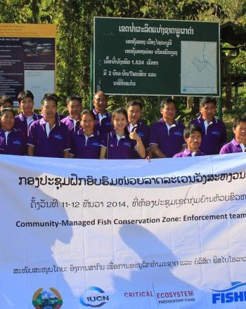 A group of about 25 men and women wearing purple shirts, standing behind signboard and holding large banner.