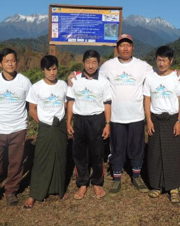 Nine people standing outside in front of sign, mountains in background.