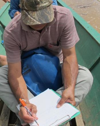 Man in canoe writes in notebook.