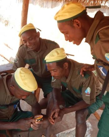 Six men in uniform, yellow caps, brown shirts and green pants, looking at small monitoring device.