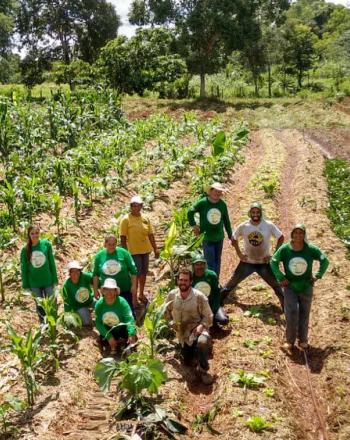 About 10 people stand in an agricultural field, smiling up at camera.