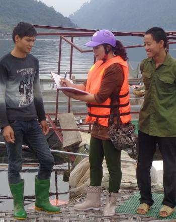 Next to water, two men stand next to woman who is writing in notebook.