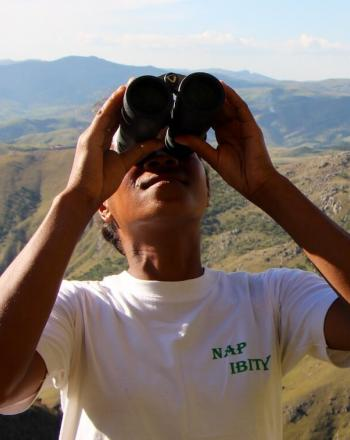 Person with NAP IBITY written on shirt looking up, through binoculars.