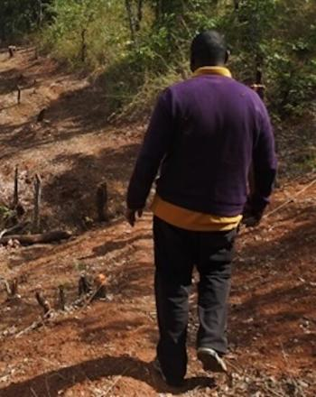 Man, back to camera, walking down bumpy dirt road.