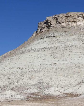Small, rocky mountain against blue sky.