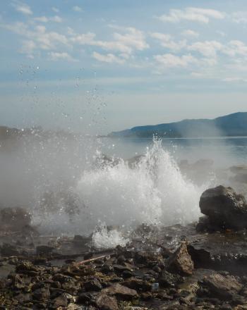 Wave crashing against rocky shore.