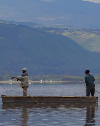 Two men standing in small boat, using long sticks to move forward.