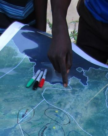 Map on table, a few people's hands holding down map, one pointing toward location..