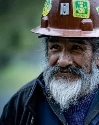 Close-up of miner with white beard wearing brown helmet looking slightly to his right.