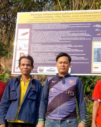 Four men standing in front of large signboard, forest behind it.