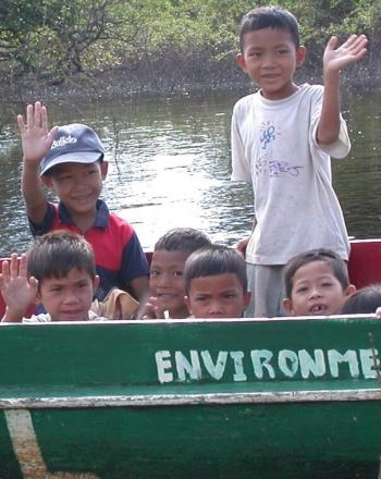 Children waving from small boat.