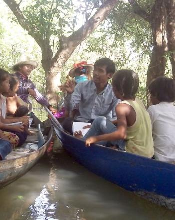 Children and teacher on two wooden canoes.