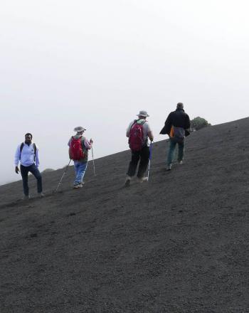 Four people climb up steep, black slope.