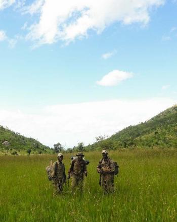 Three men standing in field, hills is background.