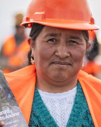 Woman with orange helmet and vest holding up informational pamplet