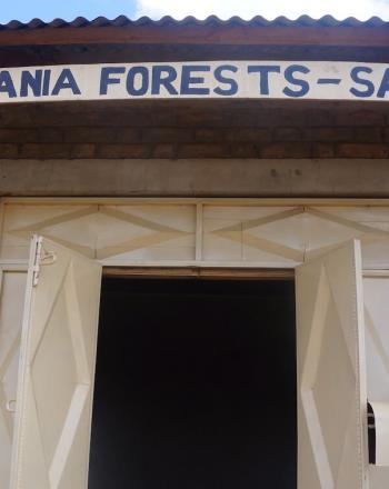 """Sign reading """"Save Tanzania Forests - SATAFO - above building door."""