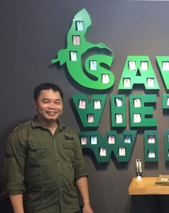 "Man standing next to large, green indoor wall sign that reads ""Save Vietnam's Wildlife."""