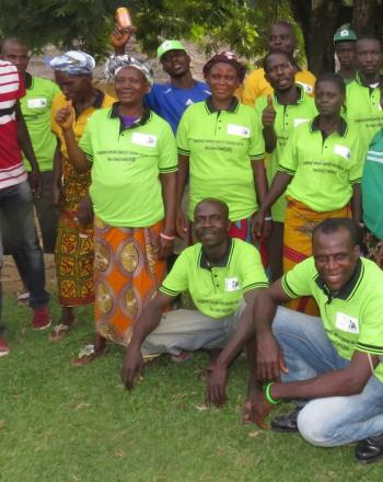 Group of about 20 people standing outside, smiling at camera. Most wear bright-green shirts.