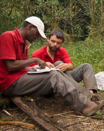 Two men sitting on forest floor, looking at notebook.