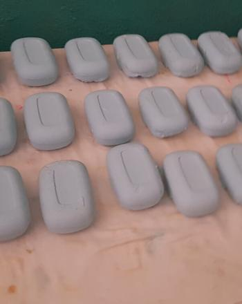 27 bars of gray soap laid out on a table.