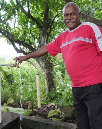 A man in an wooded area in Tafea Province, Vanuatu, uses a water spigot.