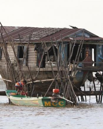 House on stilts over water, a small motorized boat with boy in front.